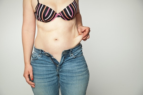 Woman in bra and jeans, pulling loose skin on her hip